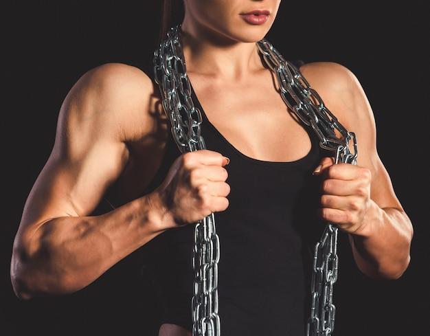 Hermosa mujer musculosa fuerte con cadena de hierro