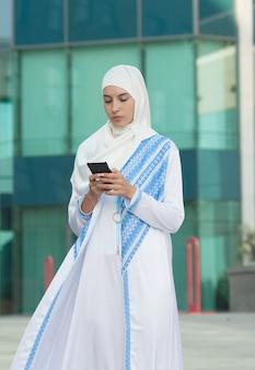Hermosa mujer musulmana mensajes de texto en un teléfono móvil al aire libre.
