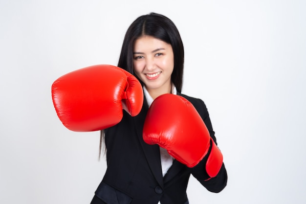 Hermosa mujer de negocios asiática con un guante de boxeo en la mano y traje de negocios