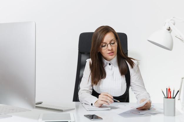 La hermosa mujer de negocios de cabello castaño serio y absorto en traje y gafas sentado en el escritorio, trabajando en la computadora con un monitor moderno con documentos en la oficina de luz,