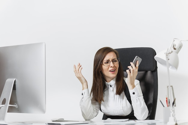 Hermosa mujer de negocios cansada y estresada en traje sentada en el escritorio, trabajando en una computadora moderna con documentos en una oficina ligera, hablando por teléfono móvil, resolviendo problemas