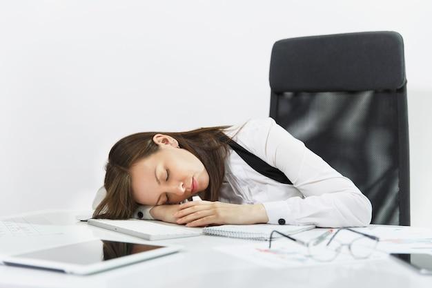 Hermosa mujer de negocios cansada, perpleja y estresada, de cabello castaño con traje y gafas, durmiendo en el escritorio después de trabajar en una computadora contemporánea con documentos en la oficina de luz