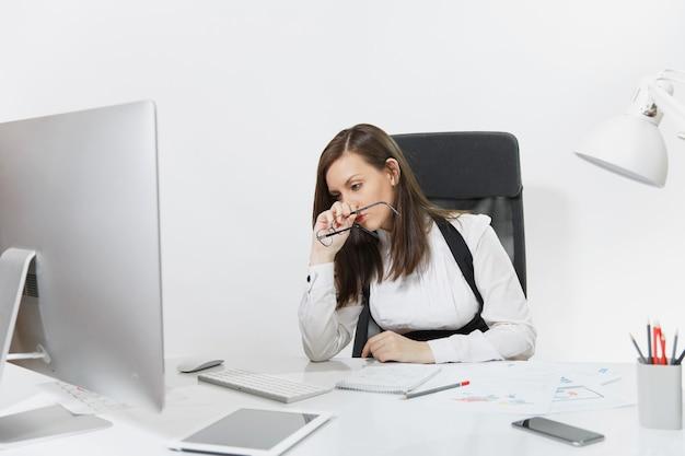 Hermosa mujer de negocios cansada, perpleja y estresada, de cabello castaño con traje y gafas, sentada en el escritorio, trabajando en una computadora contemporánea con documentos y monitor en la oficina de luz