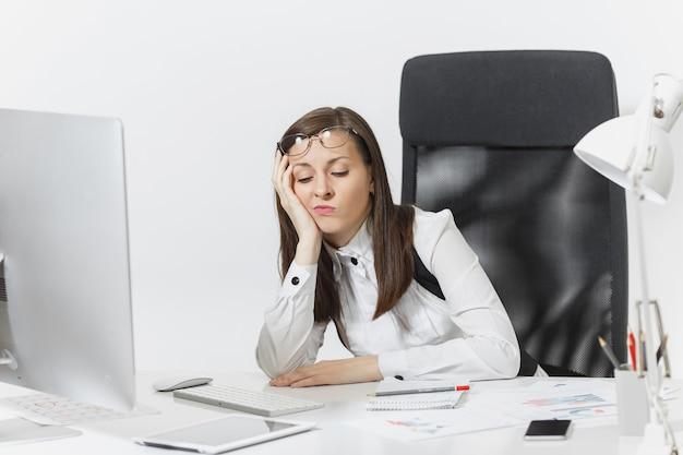 La hermosa mujer de negocios cansada, perpleja y estresada, de cabello castaño con traje y gafas, sentada en el escritorio, trabajando en una computadora contemporánea con documentos en la oficina de luz