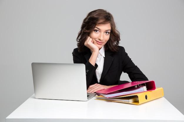 Hermosa mujer de negocios confiada rizada sonriente usando laptop y carpetas