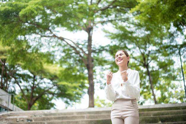 Hermosa mujer de negocios es exitosa al aire libre