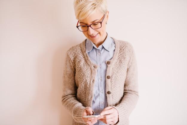 Hermosa mujer de negocios con estilo en suéter chaleco utilizando un móvil cerca de pared blanca