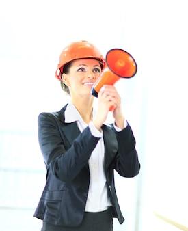 Hermosa mujer de negocios grita el ingeniero en el shoutbox sobre un fondo blanco.