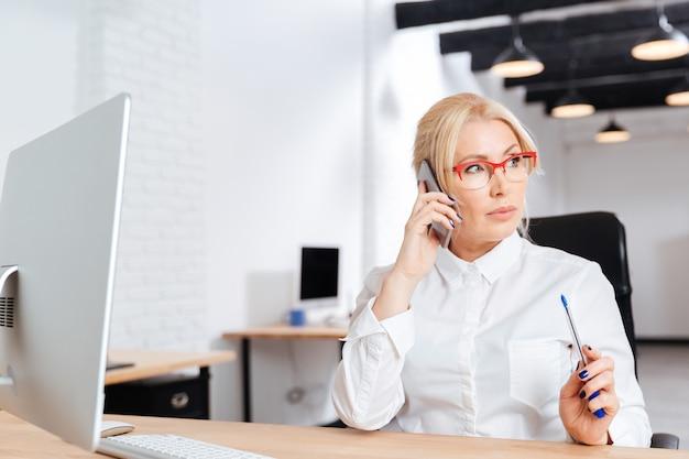 Hermosa mujer de negocios madura hablando por teléfono en la oficina