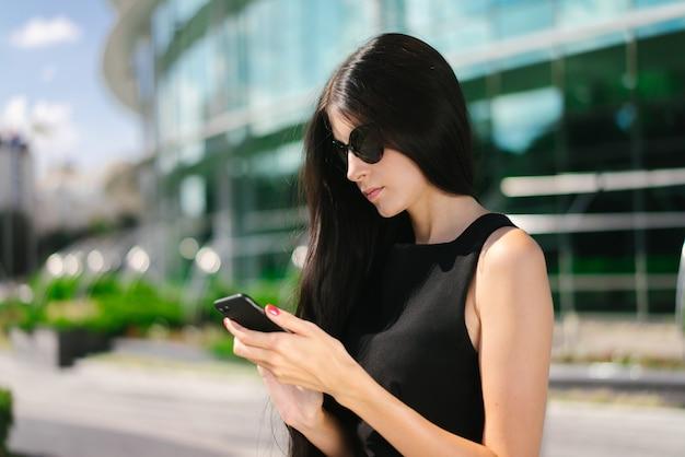 Hermosa mujer de negocios morena con elegante vestido negro y gafas de sol de pie frente al edificio de cristal de alta tecnología del centro de negocios con teléfono móvil en manos escribiendo mensaje