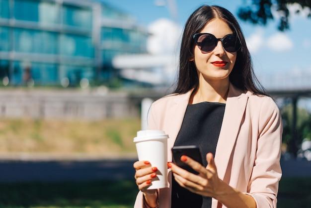 Hermosa mujer de negocios morena sonriente con elegante vestido negro, gafas de sol, con labios rojos y uñas tomando café al aire libre