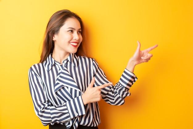 Hermosa mujer de negocios presenta algo sobre fondo amarillo