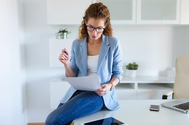 Hermosa mujer de negocios revisando documentos en la oficina.