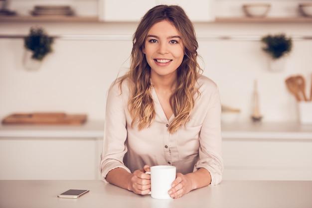 Hermosa mujer de negocios en ropa casual está sosteniendo una taza