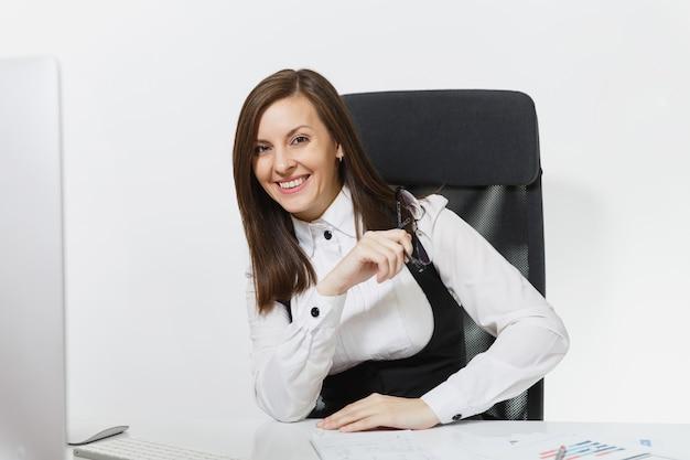 Hermosa mujer de negocios sonriente de cabello castaño en traje y gafas sentado en el escritorio, trabajando en la computadora con un monitor moderno con documentos en la oficina de luz