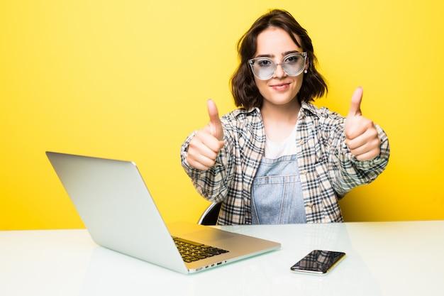 Hermosa mujer de negocios sonriente o estudiante sentada en su computadora portátil con un libro abierto junto con un gesto de pulgar hacia arriba