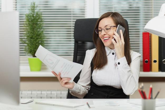 Hermosa mujer de negocios sonriente en traje y gafas sentado en el escritorio, trabajando en una computadora contemporánea con documentos en una oficina ligera, hablando por teléfono móvil, manteniendo una conversación agradable