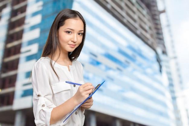 Hermosa mujer de negocios tomando notas en su portapapeles