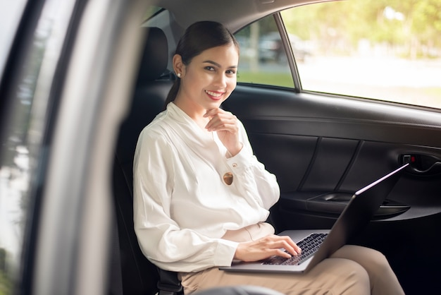 Hermosa mujer de negocios está trabajando en coche