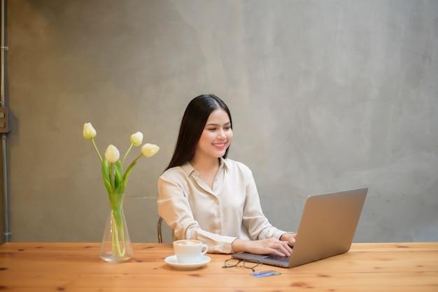 Hermosa mujer de negocios está trabajando con la computadora portátil en la cafetería
