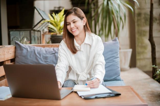 Hermosa mujer de negocios está trabajando con su computadora portátil en la cafetería