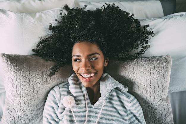 Hermosa mujer negra acostada en la cama mirando a la cámara sonriendo