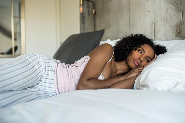 Hermosa mujer negra acostada en la cama