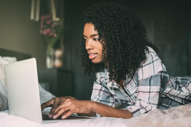 Hermosa mujer negra en cama con laptop y taza de café