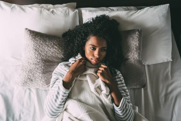 Hermosa mujer negra pensativa con el pelo rizado acostado en la cama mirando a otro lado