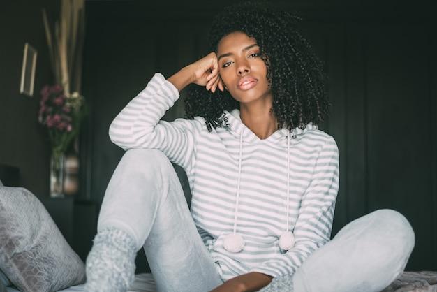 Hermosa mujer negra pensativa sentarse en la cama mirando a la cámara