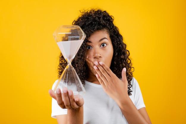 Hermosa mujer negra con reloj de arena aislado sobre amarillo