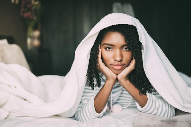 Hermosa mujer negra seria pensativa y triste que cubre su cabeza con una sábana en la cama