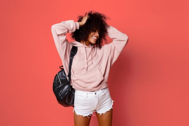 Hermosa mujer negra sexy en elegante sudadera con capucha con mochila posando sobre fondo rosa y jugando con pelos rizados.