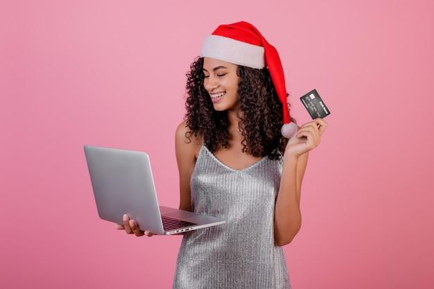 Hermosa mujer negra con tarjeta de crédito y portátil con sombrero de navidad de vacaciones y vestido aislado en rosa