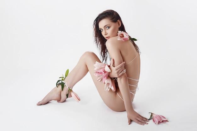 Hermosa mujer niña atadas cuerdas y flores de lirio