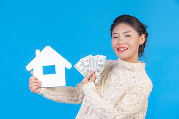 Una hermosa mujer con una nueva alfombra blanca de manga larga que contiene el símbolo de la casa y billetes de dólar en un azul. comercio .