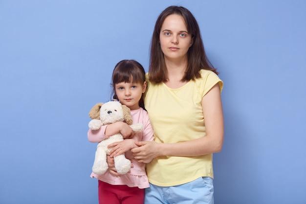 Hermosa mujer de ojos azules abrazando a su hija, niña sosteniendo su juguete favorito