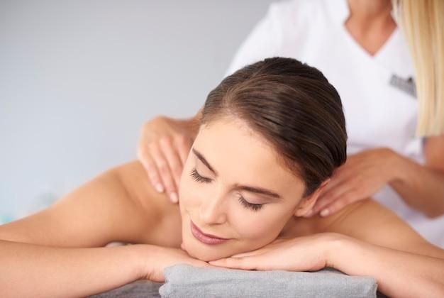 Hermosa mujer con los ojos cerrados durante el masaje de espalda