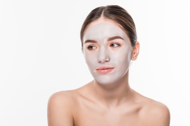 Hermosa mujer con los ojos cerrados y la máscara facial de arcilla blanca en la cara en la pared blanca