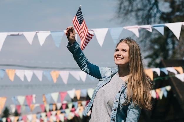 Hermosa mujer ondeando la bandera de estados unidos en el festival