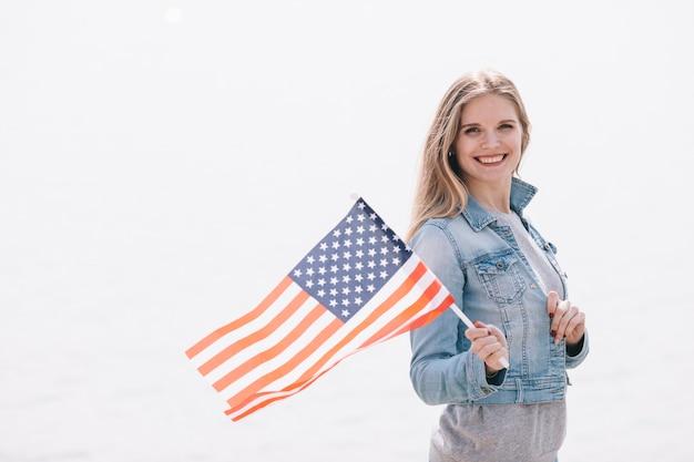 Hermosa mujer ondeando la bandera de estados unidos en palo