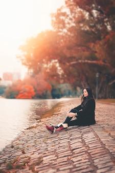 Hermosa mujer de otoño con hojas de otoño sobre fondo de naturaleza de otoño