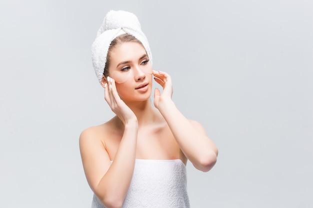 Hermosa mujer con parches para ojos en la cara, piel limpia y cosméticos