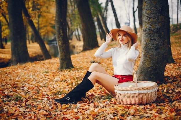 Hermosa mujer en un parque de otoño