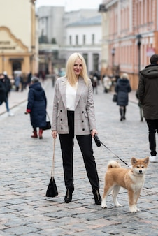 Hermosa mujer paseando a su perro en la ciudad durante el día, akita, empresaria.