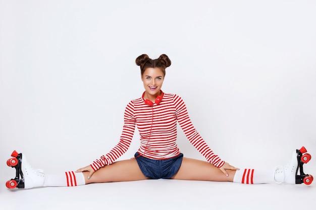 Hermosa mujer en los patines y con auriculares rojos