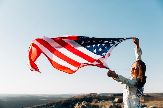 Hermosa mujer patriótica con banderas americanas revoloteando