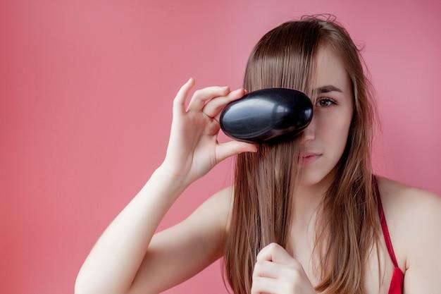 Hermosa mujer peina su cabello largo sano