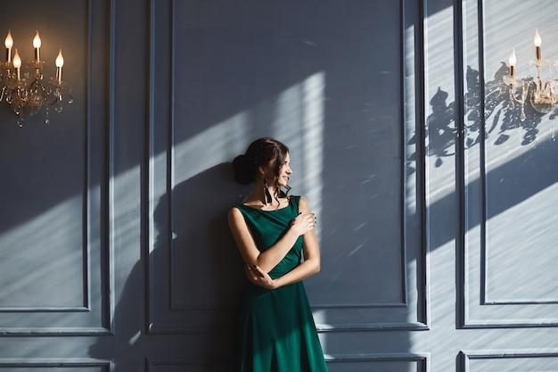 Una hermosa mujer con peinado elegante, vestido de noche verde, se encuentra en la pared azul con luz solar y sombras