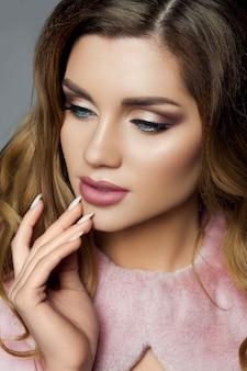 Hermosa mujer con peinado voluminoso y maquillaje perfecto.